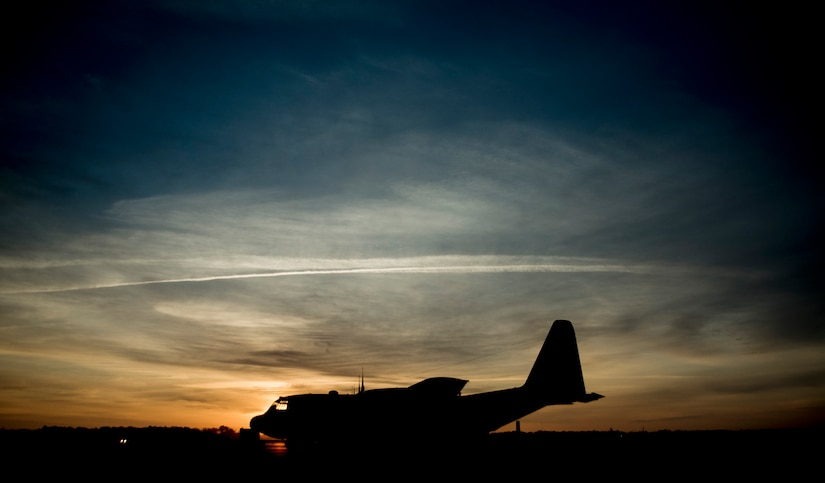 The sun rises above a C-130 Hercules March 27, 2014, at Joint Base Charleston, S.C. The aircraft is capable of operating from rough, dirt strips and is the prime transport for airdropping troops and equipment into hostile areas. The C-130 operates throughout the U.S. Air Force, serving with Air Mobility Command, Air Force Special Operations Command, Air Combat Command, U.S. Air Forces in Europe, Pacific Air Forces, Air National Guard and the Air Force Reserve Command, fulfilling a wide range of operational missions in both peace and war situations. (U.S. Air Force photo/Senior Airman Dennis Sloan)