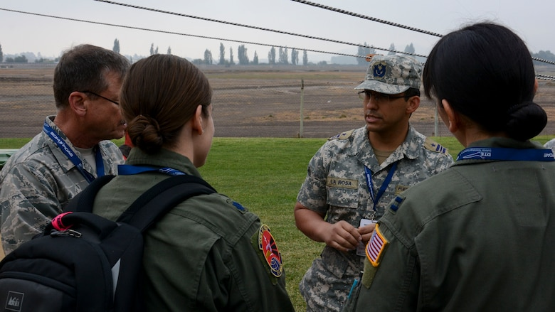 Col. Garry Moore (left), a flight surgeon with the Texas Air National Guard, Lt. Col. Kat Callaghan (center), 571st Mobility Support Advisory Squadron director of operations, and Capt. Elizabeth Peters (right), 571st MSAS aeromedical evacuation air adviser, discuss deployed medical support with a Chilean air force mofficer in Santiago, Chile, March 27. Nearly 60 U.S. airmen are participating in discussions with Chilean air force counterparts this week, and as part of the events are hosting static displays of the C-130 Hercules and F-16 Fighting Falcon during the FIDAE Air Show March 25 to 30. (U.S. Air Force photo by Capt. Justin Brockhoff/Released)