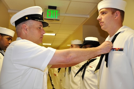 Senior Chief Petty Officer Tommy Wagers, Naval Health Clinic Charleston Directorate for Administration senior enlisted leader, adjusts Seaman Christopher Connelly's neckerchief prior to a command-wide uniform inspection March 28, 2014, at NHCC on Joint Base Charleston – Weapons Station, S.C. Connelly is a Hospital Corpsman assigned to NHCC. (U.S. Navy photo/Petty Officer 3rd Class Caralyn Mulyk)
