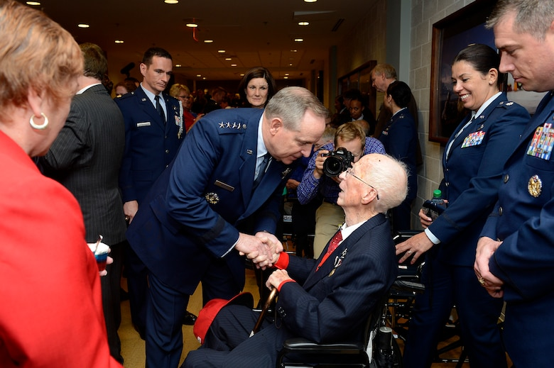 First Lt. James Mahon (seated) is congratulated by Air Force Chief of Staff Gen. Mark A. Welsh III after he received the Prisoner of War Medal April 30, 2014, during a ceremony at the Pentagon. Mahon was held in a prison camp in Wauwilermoos, Switzerland, after being shot down during a mission over Germany. (U.S. Air Force photo/Scott M. Ash)