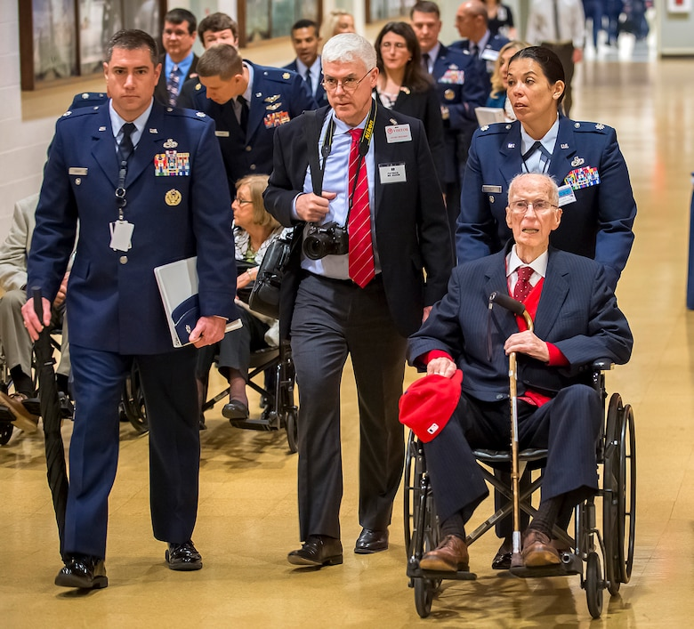 First Lt. James Mahon (seated) is escorted into the Pentagon where he received the Prisoner of War Medal from Air Force Chief of Staff Gen. Mark A. Welsh III during a ceremony April 30, 2014. Nine aviators were shot down while flying missions over Germany and held in a prison camp in Wauwilermoos, Switzerland. (U.S. Air Force photo/Jim Varhegyi)