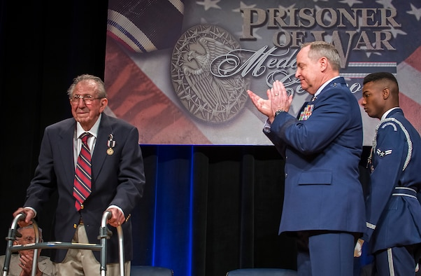 Air Force Chief of Staff Gen. Mark A. Welsh III applauds retired Lt. Col. James I. Misuraca after presenting him with the Prisoner of War Medal during a ceremony April 30, 2014, at the Pentagon. Misuraca, a former bomber crew member, was shot down while flying missions over Germany and was held in a prison camp in Wauwilermoos, Switzerland. (U.S. Air Force photo/Jim Varhegyi)