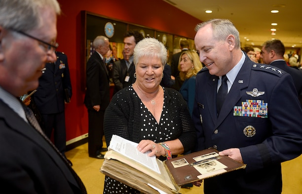 Francine Munster shows Air Force Chief of Staff Gen. Mark A. Welsh III an album containing historical documents and photographs following a POW Medal ceremony, April 30, 2014, at the Pentagon. Munster is the daughter of Col. James Mahafee, who was posthumously awarded the medal. Mahafee and eight other World War II aviators were recognized during the ceremony. The bomber crew members were shot down while flying missions over Germany and were held in a prison camp in Wauwilermoos, Switzerland. For decades, the men were denied POW status. (U.S. Air Force photo/Scott M. Ash)