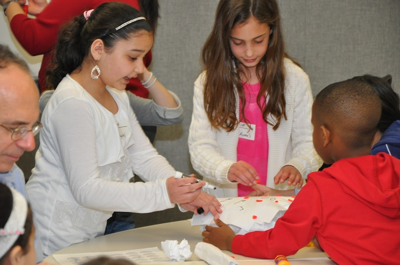 Children building a structure that can withstand the weight of a stack of books. Bring Your Child to Work Day - STEM Event