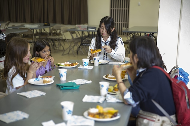 Japanese and American Girl Scouts eat pizza they made at the Marine Memorial Chapel aboard Marine Corps Air Station Iwakuni, Japan, April 25, 2014. The U.S. Girl Scouts invited their sister scouts to a cultural exchange to foster friendship and interact with one another. The girls divided into teams and had to decide how they wanted their pizza made.