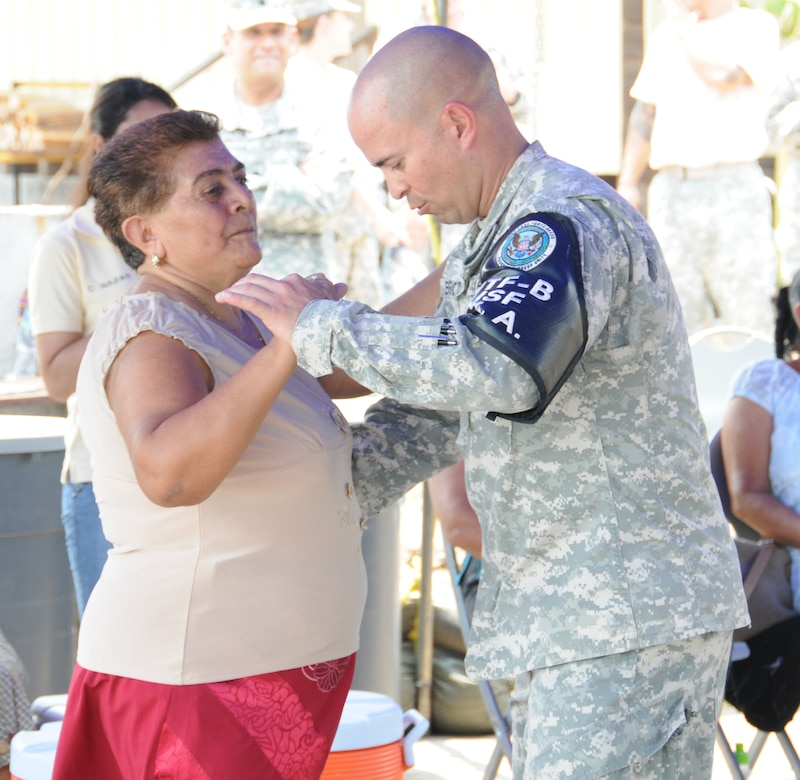 U. S. Army Sgt. Dionny Betancourt dances with a Honduran woman during the dance instructional portion of the senior health engagement.  Joint Task Force-Bravo's Medical Element (MEDEL), with support from all Joint Task Force-Bravo commands, hosted the Soto Cano Air Base Senior Health Engagement providing valuable health and wellness information, a base tour, and some entertainment to 133 Honduran senior citizens from Cane, La Paz, April 30.  The group received health screenings and patient education related to blood pressure, blood sugar, exercise, muscle strength, balance and good oral hygiene as they age.  After the screenings and classes were finished, the group of senior citizens was able to turn back the hands of time and act young again as they were treated to dance lessons and the opportunity to dance with members from Joint Task Force-Bravo.  (Photo by U. S. Air National Guard Capt. Steven Stubbs)