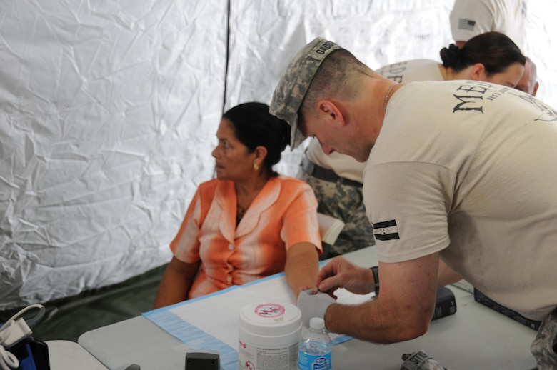 U. S. Army Maj. Scott Gadberry performs a blood sugar screening test for a Honduran woman.  Joint Task Force-Bravo's Medical Element (MEDEL), with support from all Joint Task Force-Bravo commands, hosted the Soto Cano Air Base Senior Health Engagement providing valuable health and wellness information, a base tour, and some entertainment to 133 Honduran senior citizens from Cane, La Paz, April 30.  The group received health screenings and patient education related to blood pressure, blood sugar, exercise, muscle strength, balance and good oral hygiene as they age.  After the screenings and classes were finished, the group of senior citizens was able to turn back the hands of time and act young again as they were treated to dance lessons and the opportunity to dance with members from Joint Task Force-Bravo.  (Photo by U. S. Air National Guard Capt. Steven Stubbs)