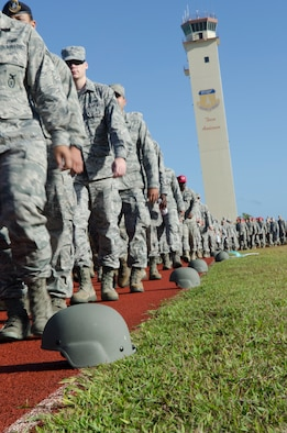 Airmen walk past helmets placed on the track during the 2014 Sexual Assault Prevention and Response Down-Day April 25, 2014, on Andersen Air Force Base, Guam. The helmets were a visual representation of individuals who have opened up reports since the implementation of the Sexual Assault Prevention and Response program at Andersen in 2006. (U.S. Air Force photo by Senior Airman Katrina M. Brisbin/Released)