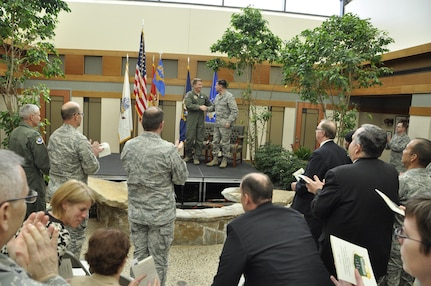 Brig. Gen. Patrick Doherty, Air Force Services director, congratulates Col. John M. Devillier, Air Force Mortuary Affairs Operations commander, May 1, 2014, at the conclusion of a ceremony commemorating the transition of AFMAO from a named activity to a Field Operating Agency, aligning the organization directly under Headquarters Air Force. (U.S. Air Force photo/Tech. Sgt. Myco Apat)