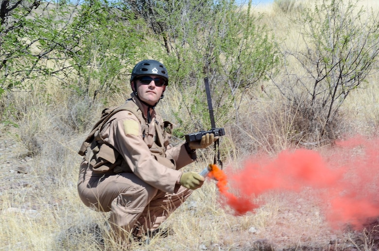 Maj. John Reed, 12th Air Force (Air Forces Southern) executive officer, uses a flare gain the attention of nearby aircraft during a Combat Search and Rescue Exercise in Southern Ariz., April 29, 2014. The main objective of this exercise was to effectively integrate communications across joint platforms to authenticate, locate and protect isolated personnel while successfully extracting them. (U.S. Air Force photo by Staff Sgt. Adam Grant/Released)