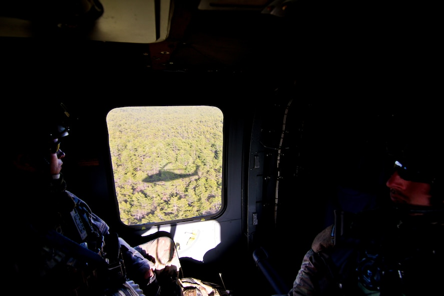 U.S. Air Force Staff Sgt. Kane Lawlor (left) and Senior Airman Sean Meehan (right) fly on a UH-60 Black Hawk helicopter from the New Jersey Army National Guard's 1-150 Assault Helicopter Battalion on April 10, 2014 over the pine barrens of N.J. Lawlor and Meehan are both tactical air control party airmen assigned to the New Jersey Air National Guard's 227th Air Support Operations Squadron. (U.S. Air National Guard photo by Tech. Sgt. Matt Hecht/Released)