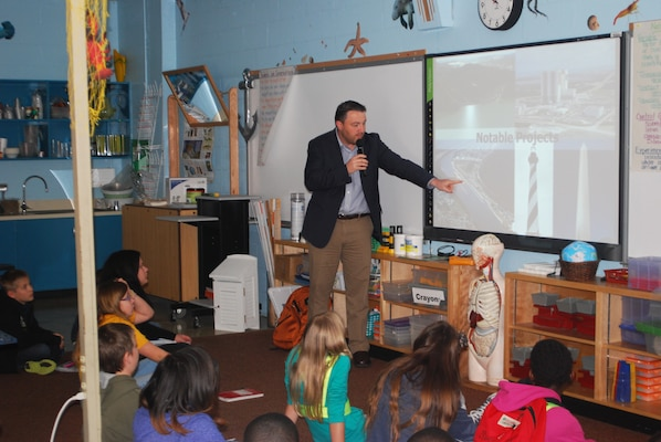 Jason Harrah, Jacksonville Harbor project manager, shows Mayport Elementary Coastal Sciences Academy fifth graders examples of projects that the U.S. Army Corps of Engineers has built across the country.