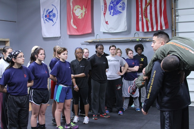 Marine Corps poolees from Recruiting Station Cleveland receive instruction on the proper positioning for a fireman's carry lift during a female pool function held at the Crossfit Box in Strongsville, Ohio, Nov. 23, 2013.  Weekly pool functions provide poolees with an intense workout and usually a question and answer period to address any questions or concerns that they may have about recruit training and the Marine Corps. (U.S. Marine Corps photo by Sgt. T.M. Stewman/Released)