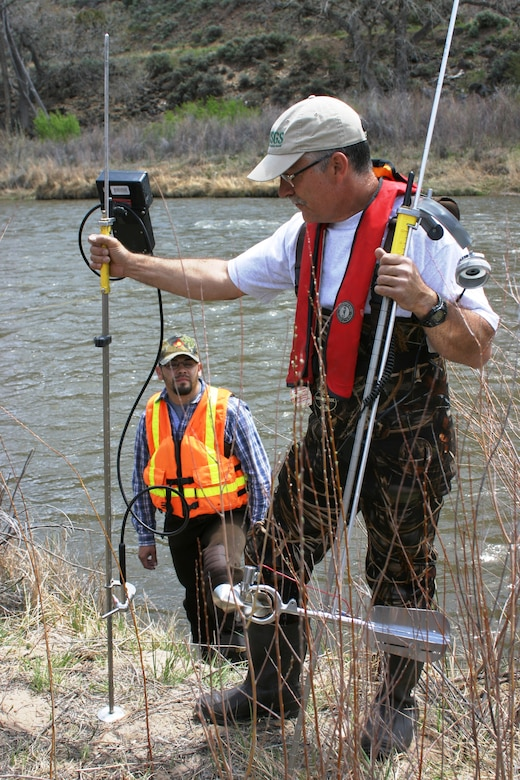 EMBUDO, N.M., -- USGS Hydrologist George Seiber holds up two different instruments for measuring stream flow.  The left one uses acoustics to measure; the instrument on the right is a traditional mechanical current meter.