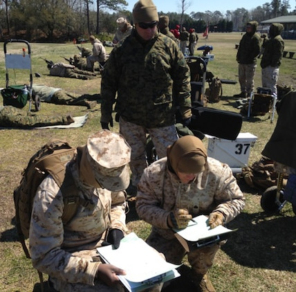 Chief Warrant Officer 3 Stephen Sutton, team member, MCLB Albany Shooting Team, observes the official scorers tallying the final scores for the team competition during the Marine Corps Eastern Division Matches held at Stone Bay, Camp Lejeune, N.C., recently.
