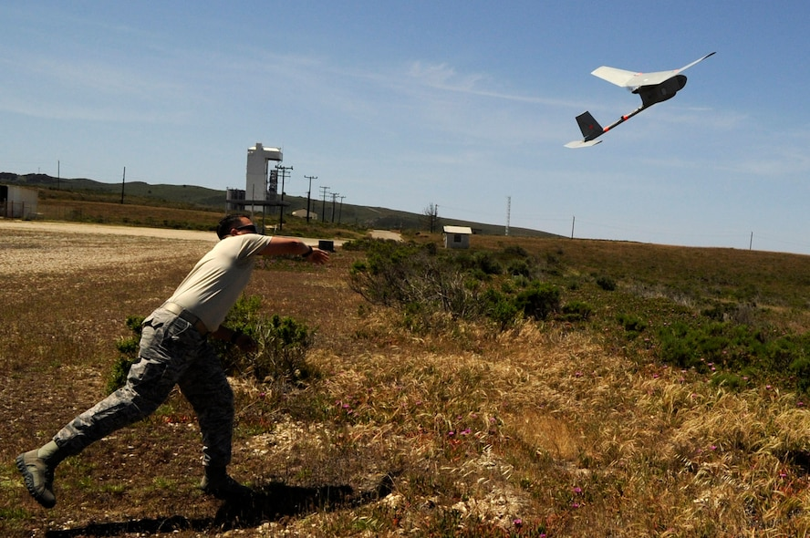 Staff Sgt. William Huster, 30th Security Forces Squadron noncommissioned officer in-charge of force protection and intelligence, launches a type of Unmanned Aerial Vehicle known as Raven-B/DDL, April 30, Vandenberg Air Force Base, Calif. The Raven requires two security forces operators and is utilized for its ample reconnaissance capabilities. (U.S. Air Force photo by Senior Airman Shane Phipps/Released)