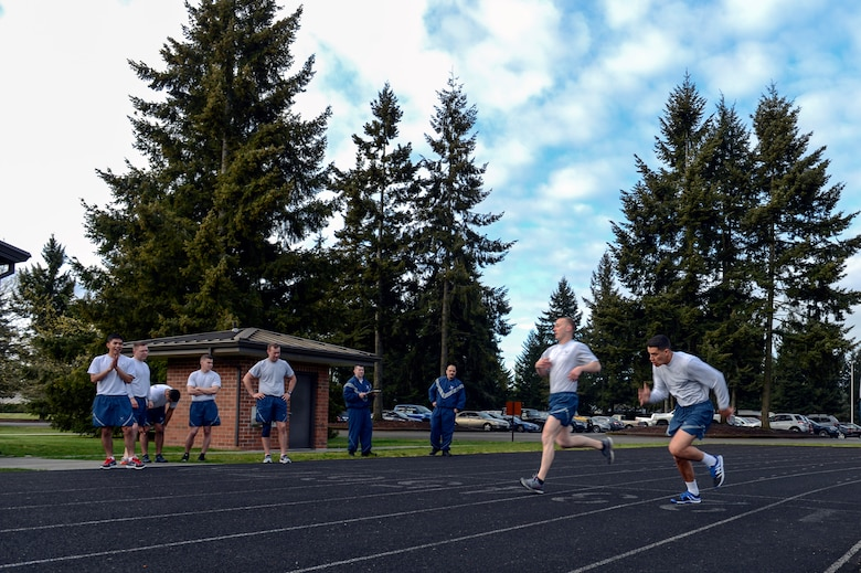 Airmen from the Civil Engineering Squadron cheer on their teammates in this month's CE Fitness Challenge April 25, 2014, at Joint Base Lewis-McChord, Wash. The 627th CES has created a unique PT program that promotes competition and focuses on improving fitness assessment scores. (U.S. Air Force photo/Airman 1st Class Jacob Jimenez)