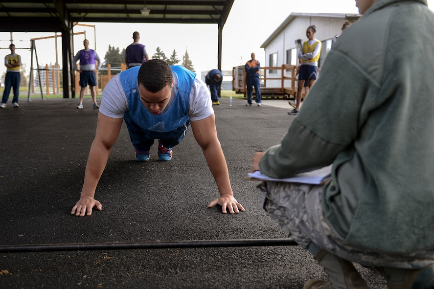 Senior Airman Christian Hill, 62nd Operations Support Squadron aircrew flight equipment journeyman, performs push-ups during his physical fitness assessment April 25, 2014, at Joint Base Lewis-McChord, Wash. Squadron unit fitness program managers on McChord Field have found different ways to keep their Airmen focused on physical training. (U.S. Air Force photo/Airman 1st Class Jacob Jimenez)