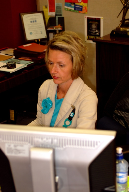 Tech. Sgt. Tina Pressy sits at her desk while wearing her teal and ribbon. The 181st Intelligence Wing has a no tolerance policy on sexual assault.