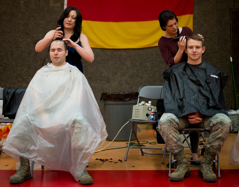 """Volunteers for """"Go Bald for Brayden"""" give haircuts to participants April 25, 2014, at Spangdahlem Air Base, Germany, during an event to show support for Brayden Mitchell, 5, recently diagnosed with a form of kidney cancer. Following Brayden's diagnosis, military members from around the globe have showed their support by shaving their heads. (U.S. Air Force photo by Staff Sgt. Chad Warren/Released)"""