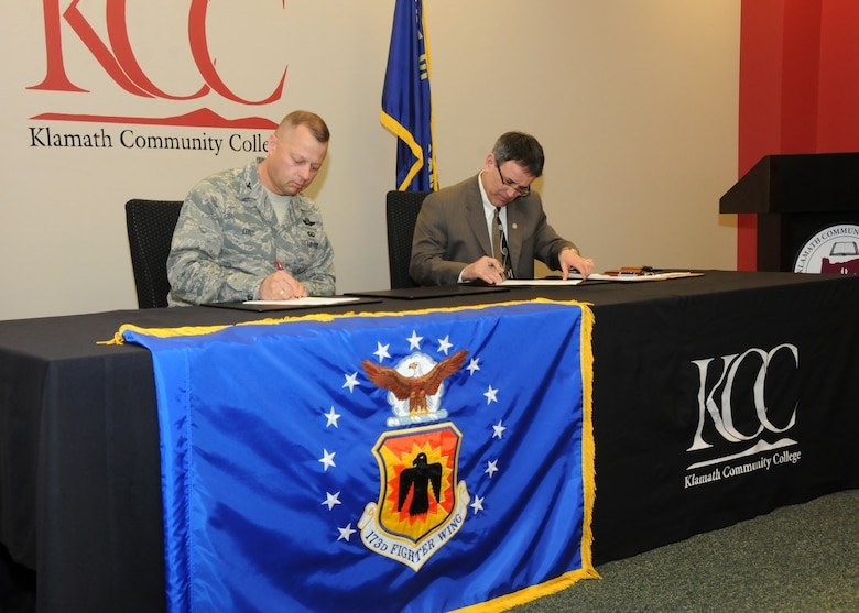 Oregon Air National Guard Col. Gregor Leist, 173rd Fighter Wing Vice Wing Commander, and Dr. Roberto Gutierrez, Klamath Community College President, sign a memorandum of understanding outlining their continuing partnership at KCC in Klamath Falls, Ore., April 16, 2014. The agreement between Kingsley Field and KCC will help members complete their Community College of the Air Force Degrees which will soon be mandatory for promotions. (U.S. Air National Guard photo by Senior Airman Penny Snoozy/Released)