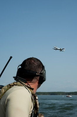 """Maj. Nathan Glasscock, Air Liaison Officer, from the 122nd Air Support Operations Squadron, Louisiana Air National Guard, calls close air support (CAS) to the A-10 Thunderbolt II aircraft above. The 190th Fighter Squadron """"Warthog"""" pilots trained with the CAS missions on the Toledo Bend Army recreational lake March 19 while deployed to Barksdale Air Force Base. (Air National Guard photo by Master Sgt. Becky Vanshur)"""