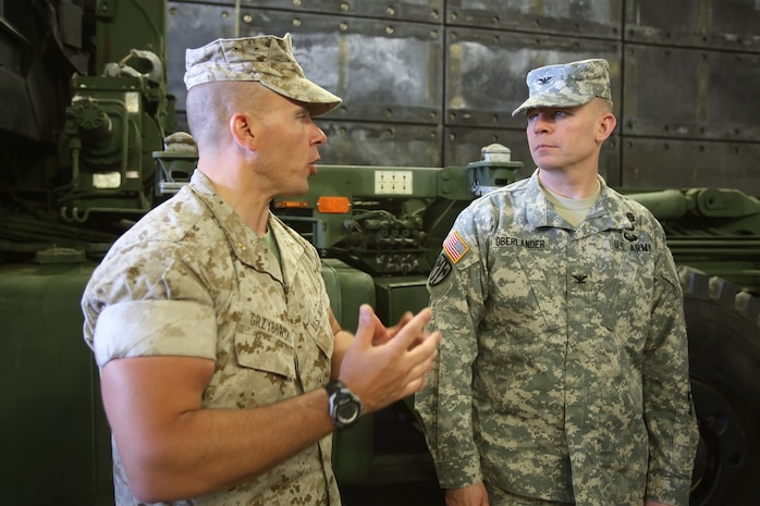 Major Shawn Grzybowski, operations officer with Headquarters Regiment, 1st Marine Logistics Group, explains his unit's logistics and transportation capabilities to Col. David Oberlander, right, protection chief with I Corps, during a Defense Support of Civil Authorities conference aboard Naval Base San Diego, Calif., April 29, 2014. The two-day event provided the opportunity for supporting agencies, partners and stakeholders to meet and discuss ideas that would reinforce relations and garner awareness of support goals and supporting agency abilities during local and national disasters. The blue-green team, including servicemembers from the Third Fleet, I Marine Expeditionary Force and 3rd Marine Aircraft Wing, educated attendees about existing and future capabilities to support disaster relief through conferences and displays of military tactical vehicle, aircraft and equipment.