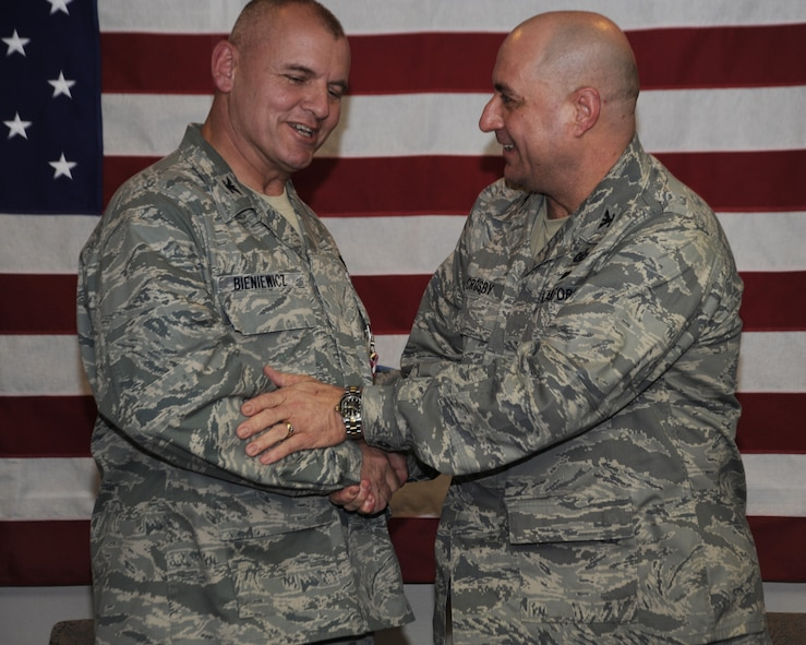Col. Michael Bieniewicz, left, outgoing Combat Operations Group (COG) Commander, shakes hands with Col. Mark Crosby, the new COG commander during the Change of Command ceremony, May 3, 2014, Portland Air National Guard Base, Ore. (Air National Guard photo by Tech. Sgt. John Hughel, 142nd Fighter Wing Public Affairs/Released)