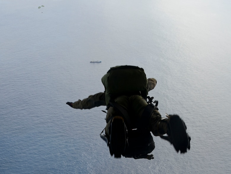 A U.S. Air Force pararescue Airman from the 48th Rescue Squadron parachutes into the Pacific Ocean to aid to two critically injured sailors aboard a Venezuelan fishing boat May 3, 2014. The Airmen flew in two HC-130J Combat King II aircraft and three HH-60 Pavehawk helicopters for nearly 11 hours, and then parachuted into the ocean 1,100 nautical miles from the Mexican coast with two inflatable zodiac boats and medical equipment to deliver lifesaving care. (U.S. Air Force photo by Staff Sgt. Adam Grant/Released)