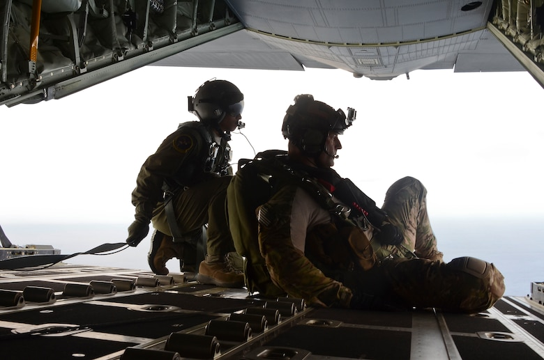 Airman 1st Class Franscisco Harper, left, and a pararescue Airman survey the area as U.S. Air Force pararescue forces parachute into the Pacific Ocean to aid to two critically injured sailors aboard a Venezuelan fishing boat May 3, 2014. The pararescue Airmen flew in two HC-130J Combat King II aircraft and three HH-60 Pavehawk helicopters for nearly 11 hours, and then parachuted into the ocean along with two inflatable zodiac boats and medical equipment to deliver lifesaving care. Harper is a loadmaster assigned to the 79th Rescue Squadron and the pararescue Airmen involved in the operation are from the 48th Rescue Squadron. (U.S. Air Force photo by Staff Sgt. Adam Grant/Released)