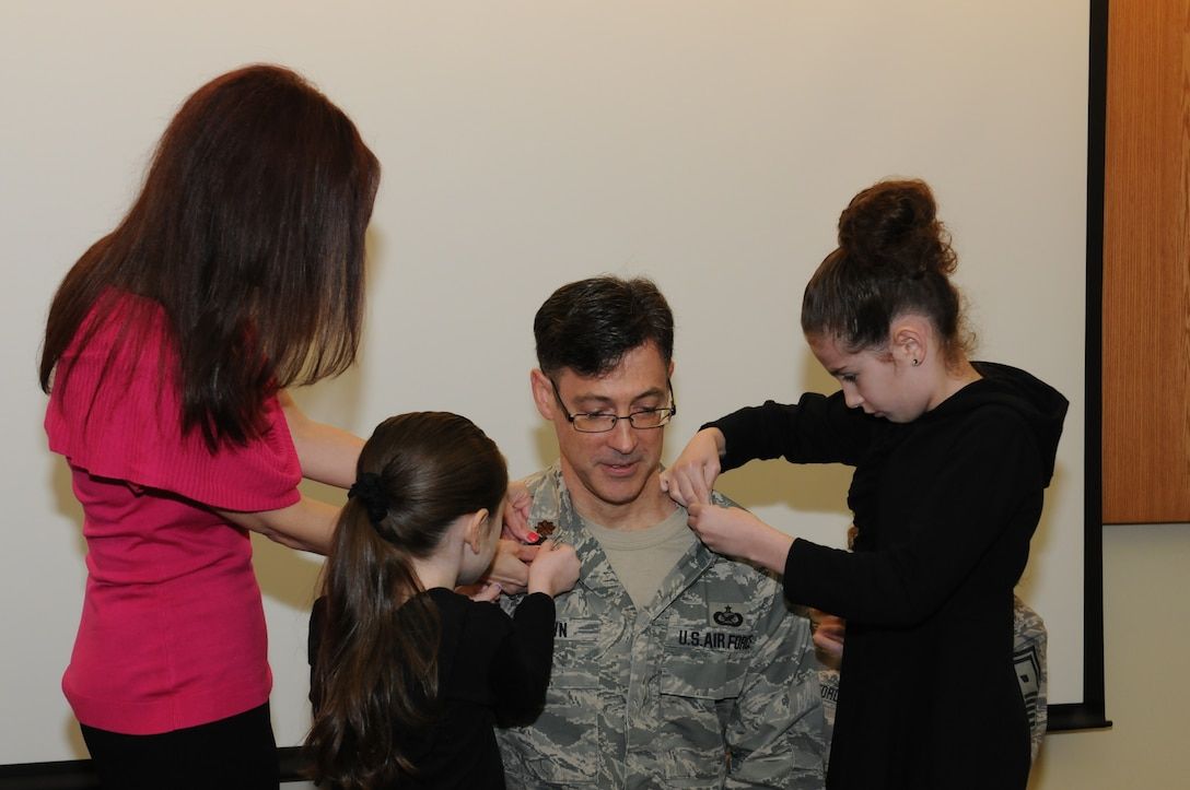 Lt. Col. Brown's wife and daughters pin on his new rank during his promotion ceremony on May 3, 2014. (Photo by New York Air National Guard Tech. Sgt. Justin A. Huett)