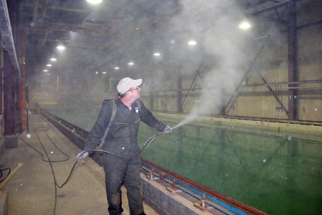 """CRREL's Jesse Stanley, Engineering Resources Branch, establishes the air moisture conditions necessary to grow seasonal """"brash"""" ice (annual pack ice in the process of melting) in the Test Basin."""