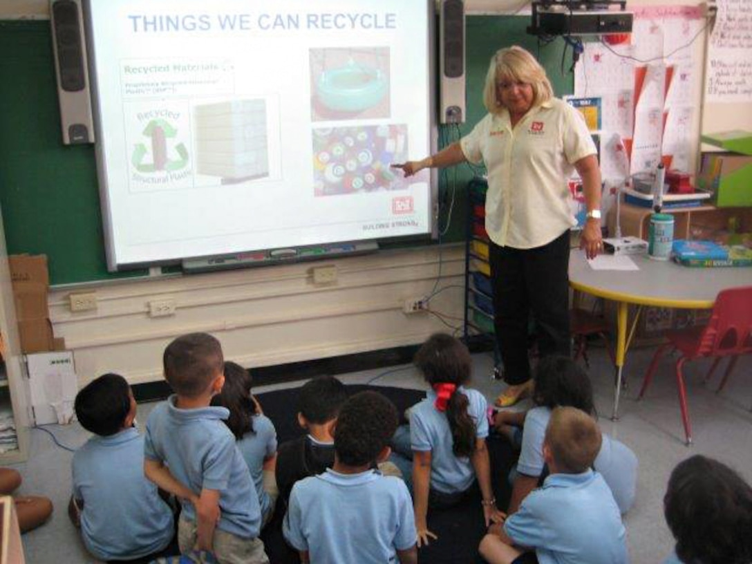 Carmen Martir, chief, administrative services in the Antilles Office, teaches first grade students at the Antilles Elementary School about the importance of recycling.