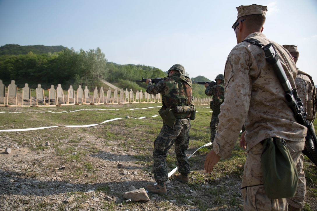 Republic of Korea Marine Pfc. Bae Jun Yeok, center, engages a target while U.S. Marine Cpl. Steven R. Bohez, right, supervises May 1 during Korean Marine Exchange Program 14-6 in Pohang, Republic of Korea. The U.S. Marine Corps Combat Marksmanship Program is designed to make Marines more proficient when engaging enemies in a hostile situation. Bae is a Daegu, Republic of Korea, native and generator operator with 1st ROK Marine Engineer Battalion, 1st ROK Marine Division. Bohez is a Detroit, Mich., native and combat engineer with 9th Engineer Support Battalion, 3rd Marine Logistics Group, III Marine Expeditionary Force.