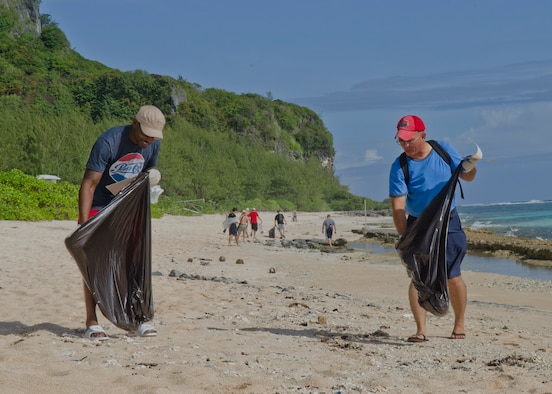 Master Sgt. Paul Johnson (left), 644th Combat Communications Squadron supply NCO in charge, and Tech. Sgt. Edward Mendiola, 254th RED HORSE HVAC technician, pick up trash along Tarague Beach during the 2nd Annual Earth Day Cleanup on Andersen Air Force Base, Guam, April 26, 2014. Approximately 35 volunteers picked up two truckloads of recyclable materials and refuse, ranging from cans to a tire. (U.S. Air Force photo by Senior Airman Katrina Brisbin/Released)