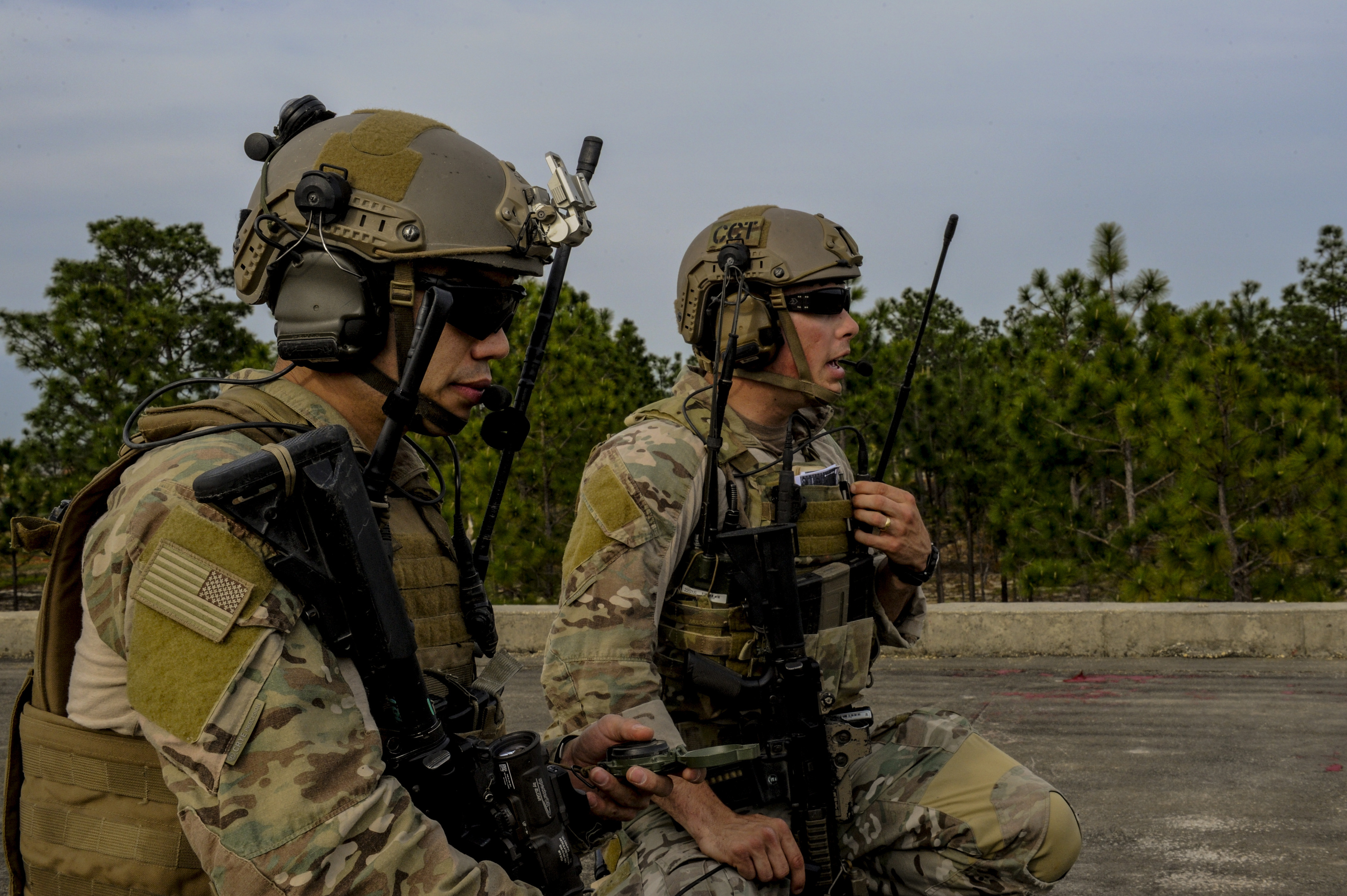 a us air force tactical air control party member left observes the compass and the area while a us air force combat controller talks on the radio for