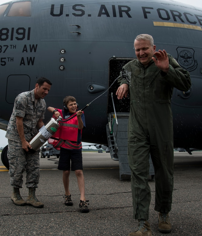"""Col. Darren Hartford gets sprayed by his son Matthew with the assistance of Staff Sgt. David Glowacki, 437th Operations Support Squadron weather forecaster, after finishing his final flight as the 437th Airlift Wing commander May 5 2014, on the flightline at Joint Base Charleston, S.C. The final or """"fini flight,"""" is an aviation tradition in which aircrew members are met by their unit comrades, family and friends and soaked with water. (U.S. Air Force photo/ Airman 1st Class Clayton Cupit)"""