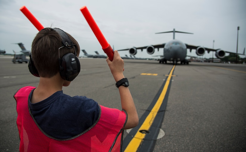 """Matthew Hartford, Col. Darren Hartford's son, marshals in a C-17 Globemaster III with the assistance of an Airman May 5, 2014, on the flightline at Joint Base Charleston, S.C. Hartford was piloting the C-17 for his final flight as the 437th Airlift Wing commander. The final or """"fini flight,"""" is an aviation tradition in which aircrew members are met by their unit comrades, family and friends and soaked with water. (U.S. Air Force photo/ Airman 1st Class Clayton Cupit)"""