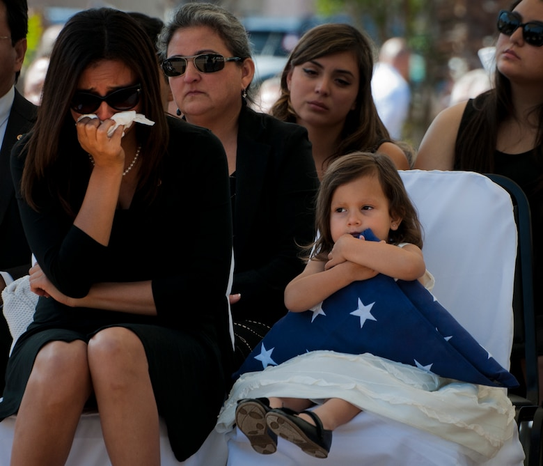 Vicki Baker, widow of Sgt. 1st Class Jeffrey Baker, weeps while their daughter, Audrey, holds a flag presented to her during the 45th Annual Explosive Ordnance Disposal Memorial Ceremony May 3, at Eglin Air Force Base, Fla. Eight new names of Army and Marine EOD technicians, who lost their lives, were added to the Memorial Wall this year.  The all-service total now stands at 306. (U.S. Air Force photo/Tech. Sgt. Sam King)