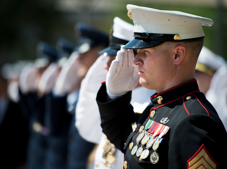 A Marine salutes during the retiring of the colors at the 45th Annual Explosive Ordnance Disposal Memorial Ceremony May 3, at Eglin Air Force Base, Fla. Eight new names of Army and Marine EOD technicians, who lost their lives, were added to the Memorial Wall this year.  The all-service total now stands at 306. (U.S. Air Force photo/Tech. Sgt. Sam King)