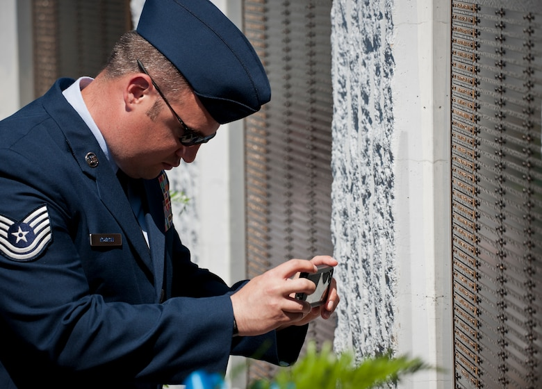 An Airman takes a photo of a name of one of the fallen explosive ordnance disposal technicians listed on the memorial wall after the 45th Annual EOD Memorial Ceremony May 3, at Eglin Air Force Base, Fla. Eight new names of Army and Marine EOD technicians, who lost their lives, were added to the Memorial Wall this year. The all-service total now stands at 306.  (U.S. Air Force photo/Tech. Sgt. Sam King)