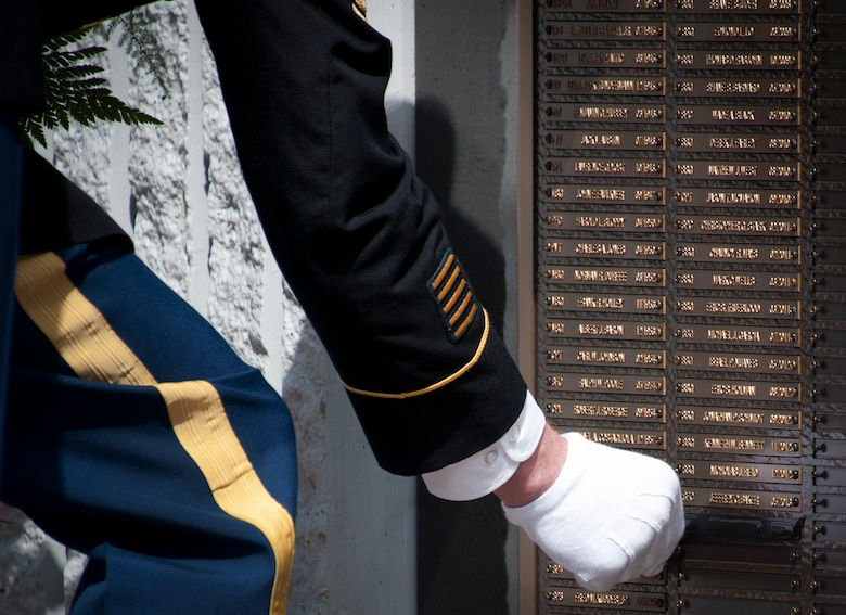 Sgt. Maj. Brian Curtis reveals a new name to the Explosive Ordnance Disposal Memorial Wall during the 45th Annual EOD Memorial Ceremony May 3, at Eglin Air Force Base, Fla. Eight new names of Army and Marine EOD technicians, who lost their lives, were added to the wall this year.  The all-service total now stands at 306. (U.S. Air Force photo/Tech. Sgt. Sam King)