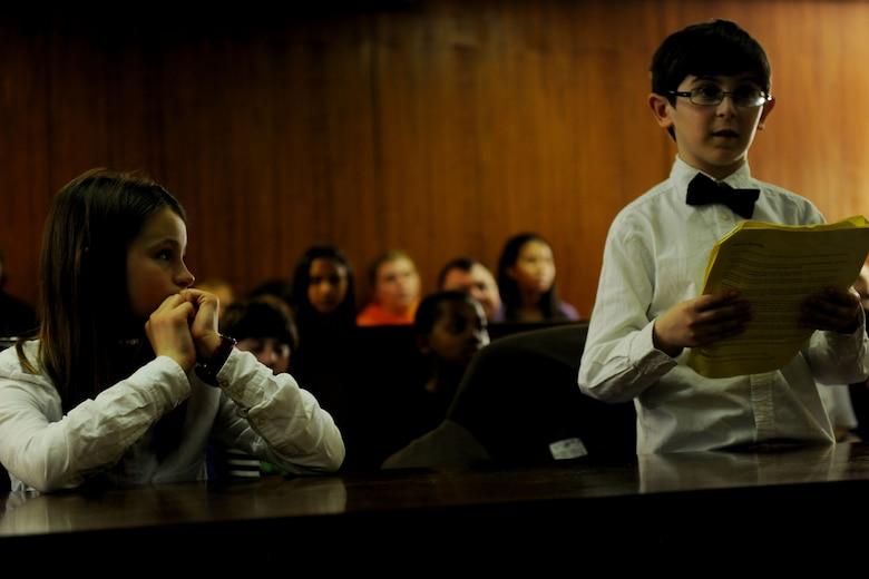 "Brenna Kjorness, left, watches as her fellow prosecutor, Eli Morris, reads his opening argument during ""The Trial of the Big Bad Wolf,"" at RAF Alconbury, United Kingdom, May 1, 2014. Kjorness and Morris, both students at Alconbury Elementary School, played roles during the mock trial as part of the 2014 Law Day Event. (U.S. Air Force photo by Staff Sgt. Jarad A. Denton/Released)"