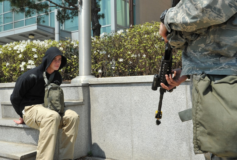 Airman 1st Class Cody Linday, left, 51st Security Forces Squadron entry controller, acts as a detained member of opposition forces while A1C David Diez, 51st SFS entry controller, guards him during Operational Readiness Exercise Beverly Bulldog 14-02 at Osan Air Base, Republic of Korea, May 5, 2014. Staff Sgt. Juan Valles, 51st SFS area supervisor, was also part of the training scenario that required himself and Diez to wait for Office of Special Investigations personnel to reach the scene and interrogate their detainee. (U.S. Air Force photo/Airman 1st Class Ashley J. Thum)