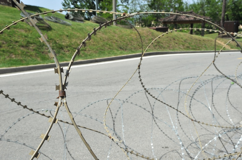 Concertina wire unfolds around Bldg. 1097 during Operational Readiness Exercise Beverly Bulldog 14-02 at Osan Air Base, Republic of Korea, May 5, 2014. The 51st Security Forces Squadron began implementing increased security measures around Bldg. 1097 to mitigate the chance of opposition forces infiltrating the area. (U.S. Air Force photo/Airman 1st Class Ashley J. Thum)