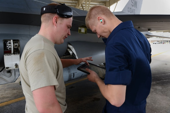 U.S. Air Force Airman 1st Class Dominic Vaughn explains to Airman Eric Bain how to navigate an iPad version of a technical order manual at Shaw Air Force Base, S.C.,  April 29, 2014. Both are 20th Aircraft Maintenance Squadron tactical aircraft maintainers (U.S. Air Force photo by Airman 1st Class Jensen Stidham)