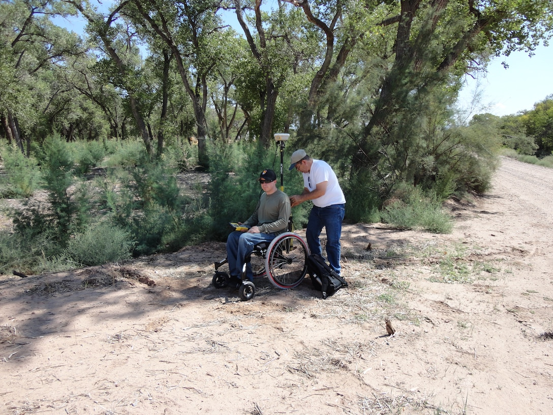 BERNALILLO COUNTY, N.M., -- Albuquerque District employee Ronnie Casaus sets up survey equipment on Bryan Estvanko's off-road wheelchair to survey material quantities on the Rio Grande Bosque Levee on Sept. 23, 2012. Photo by Gary Edwards.