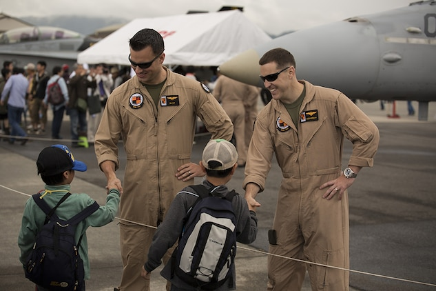 Capt. Brian Hall, left, and Capt. Ted Lindell, right, shake hands with Japanese boys, after posing for a photo in front of an F/A-18, during Friendship Day at Marine Corps Air Station Iwakuni, Japan, May 5, 2014. Hall and Lindell are aviators with Marine Attack Squadron 224, currently stationed at MCAS Iwakuni under the Unit Deployment Program. Friendship Day is an event that allows Japanese citizens a chance to see military vehicles and aircraft, meet American service members and get a taste of American culture.