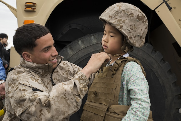 Cpl. Jose Escribano puts a Kevlar helmet onto a Japanese boy during Friendship Day at Marine Corps Air Station Iwakuni, Japan, May 5, 2014. Escribano is a motor transportation operator with Marine Wing Support Squadron 171, and was just one of the many Marines that helped host more than 50,000 visitors. Friendship Day is an event that allows Japanese citizens a chance to see military vehicles and aircraft, meet American service members and get a taste of American culture.
