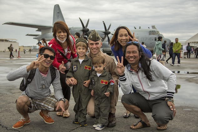 Capt. Matthew Sisneros, center, and his children, Adam and Max, pose with patrons during Friendship Day aboard Marine Corps Air Station Iwakuni, Japan, May 5, 2014. Sisneros is an aviator with Marine All Weather Fighter Attack Squadron 242. Friendship Day is an event that allows Japanese citizens a chance to see military vehicles and aircraft, meet American service members and get a taste of American culture.